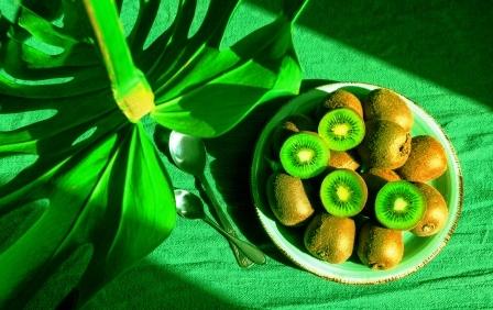 ovocie kivi na tanieri s tropickymi listami monstera