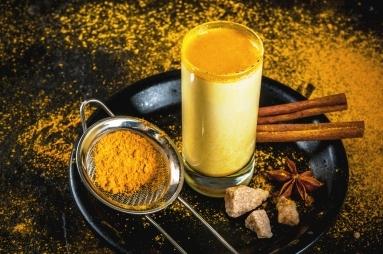 zlaté kurkumové mléko v skleničce a prášek z kurkumy a lékořicí