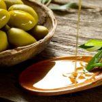 olivový olej na dřevěné lžičce, listy olivovníka a čerstvé olivy v misce