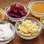fermentované potraviny v miskách - jablční ocet, okurka, řepa, zelí