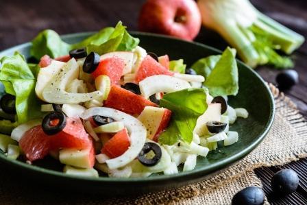 stonkový celer salát na talíři - grapefruit, olivy, fenikl, jabko a stonkový celer