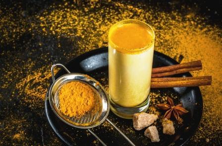 zlaté mléko v pohári - kurkuma, rostlinné mléko, lékořice na černé tácke, v pozadí prášek z kurkumy