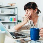 žena zíva při počítaci, v ruce drží šálku kávy