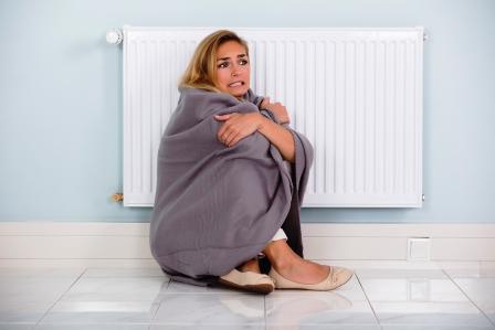 žene je zima, sedí při radiatore a je zabalená v dece