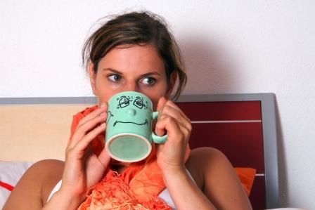 chorá žena leží v posteli a pije ze šálky