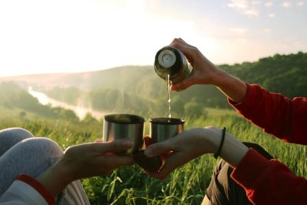 dvaja lidi pijí bylinkový čaj s medem z termosky