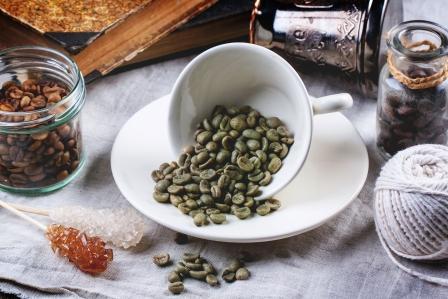 Šálka zelených nepražených kávových zrn na stole se starožitnými knihami a jými druhy kávy