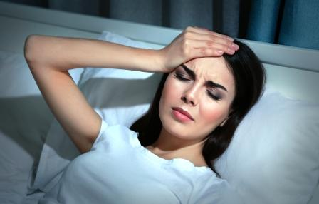 mladá žena trpí bolestí hlavy, leží v posteli