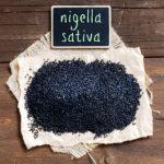 černucha, čierné semena na dřevěném stole